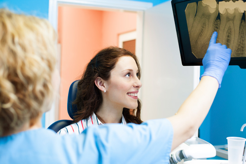 A patient looking at their digital x-rays with a doctor at Alexandra Garcia, DDS in Houston, TX.