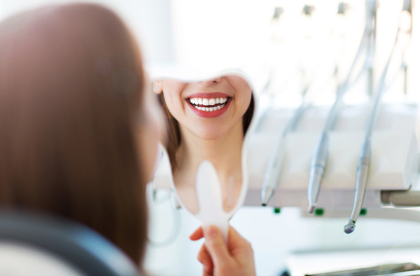 Woman smiling in mirror after restorative dentistry services from Alexandra Garcia, DDS