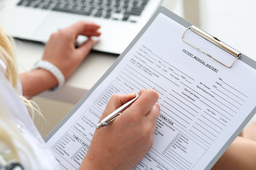 A woman filling out a new patient form at Alexandra Garcia, DDS, MS in Houston, TX